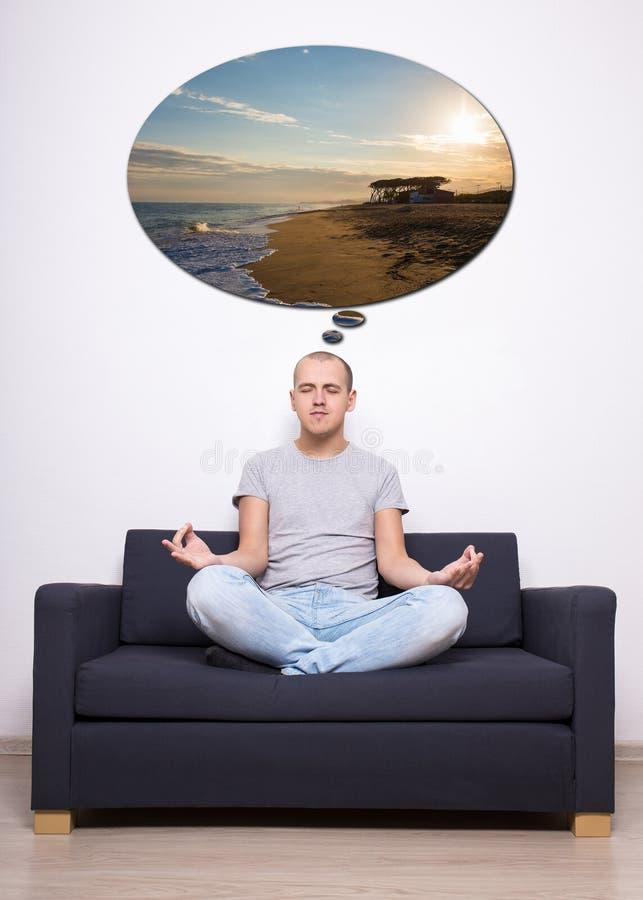 Conceito da meditação - homem cansado que senta-se no sofá na pose da ioga e imagem de stock
