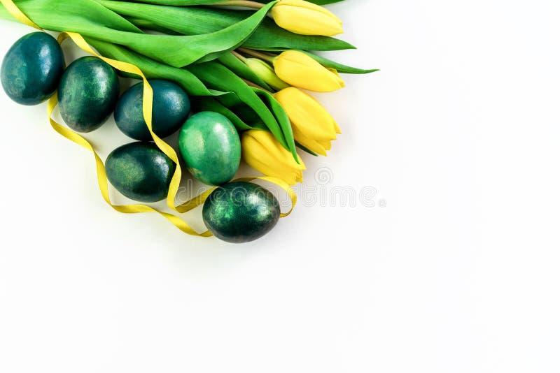 Conceito da mola com ovos da p?scoa e as tulipas amarelas no fundo branco isolado Copie o espa?o imagens de stock royalty free