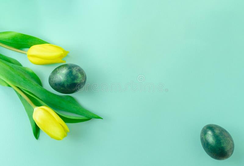 Conceito da mola com ovos da p?scoa e as tulipas amarelas no fundo do azul de turquesa Configura??o lisa Copie o espa?o fotografia de stock royalty free