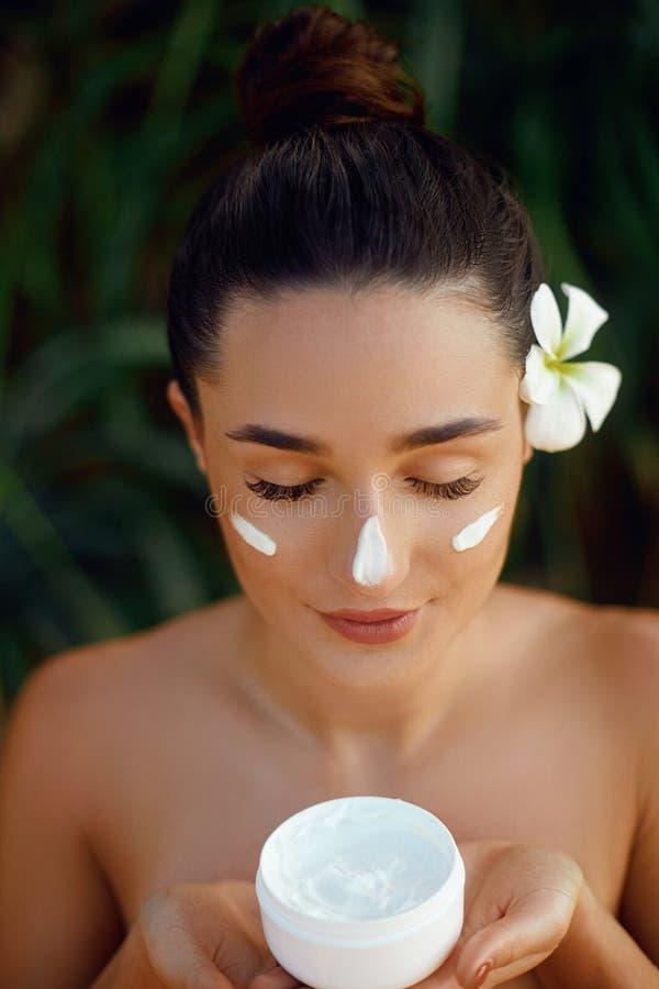 Conceito da mulher da beleza Cuidado de pele Retrato do modelo fêmea que guarda e que aplica o creme hidratando cosmético fotos de stock royalty free