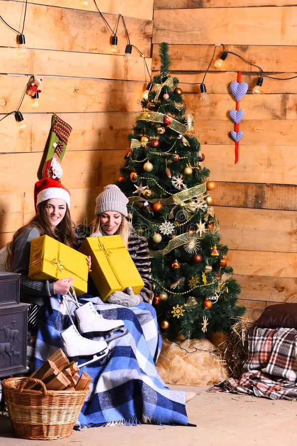 Conceito da Noite de Natal As meninas com caras felizes aproximam a árvore de Natal imagem de stock