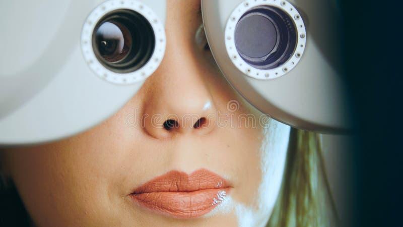 Conceito da oftalmologia - a jovem mulher verifica os olhos no equipamento moderno no centro médico fotografia de stock