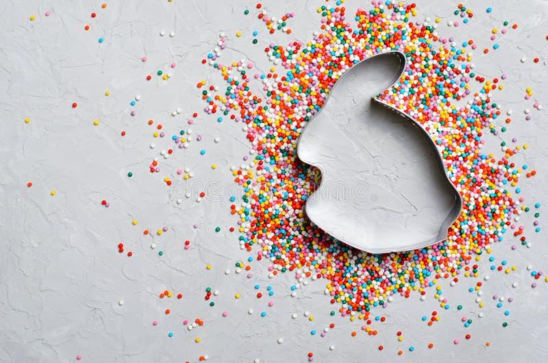 Conceito da Páscoa, Sugar Sprinkles e cortador da cookie em Grey Background imagem de stock royalty free