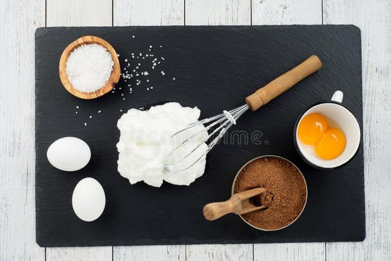 Conceito da padaria, ingredientes para fazer o bolo de chocolate no fundo de madeira branco, vista superior fotografia de stock