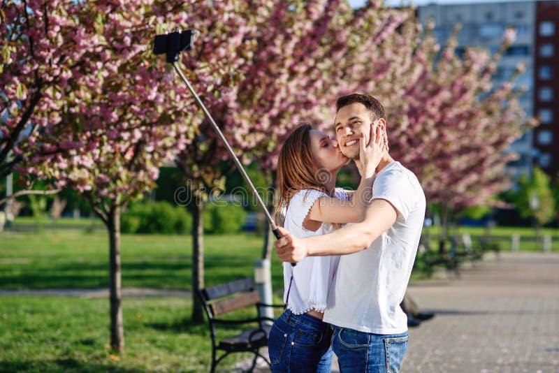 Conceito da paixão e do amor Homem e mulher que beijam no jardim de florescência no dia de mola Acople abraços perto das árvores  imagem de stock royalty free