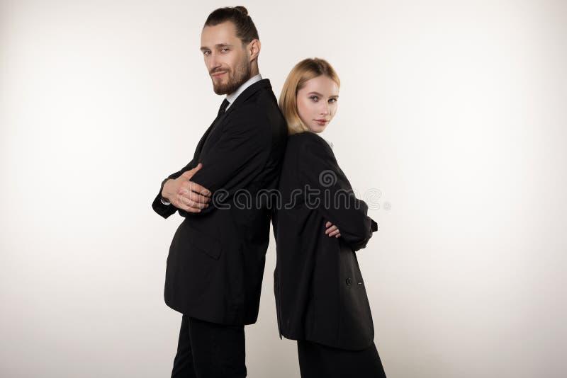 Conceito da parceria no negócio Homem considerável e mulher bonita, nos ternos pretos que estão de volta à parte traseira com imagem de stock royalty free