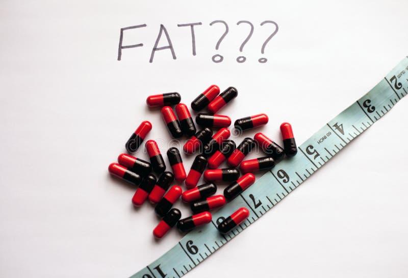 Conceito da perda de peso com os comprimidos gordos do queimador e uma fita de medição fotos de stock royalty free