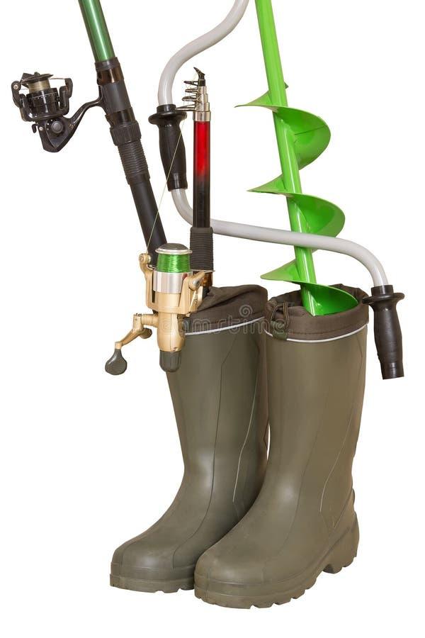 Conceito da pesca: as varas de pesca e o gelo da mão furam dentro as botas de borracha no fundo branco fotografia de stock