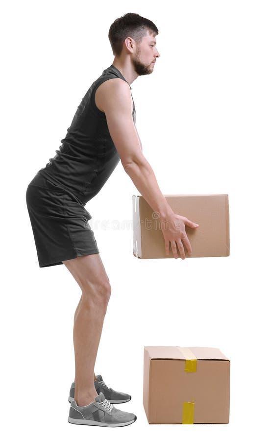 Conceito da postura Homem que levanta a caixa de cartão pesada fotos de stock