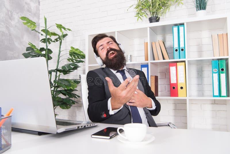 Conceito da produtividade Homem de neg?cios bem sucedido Fones de ouvido de escuta da música do trabalhador de escritório do home fotos de stock