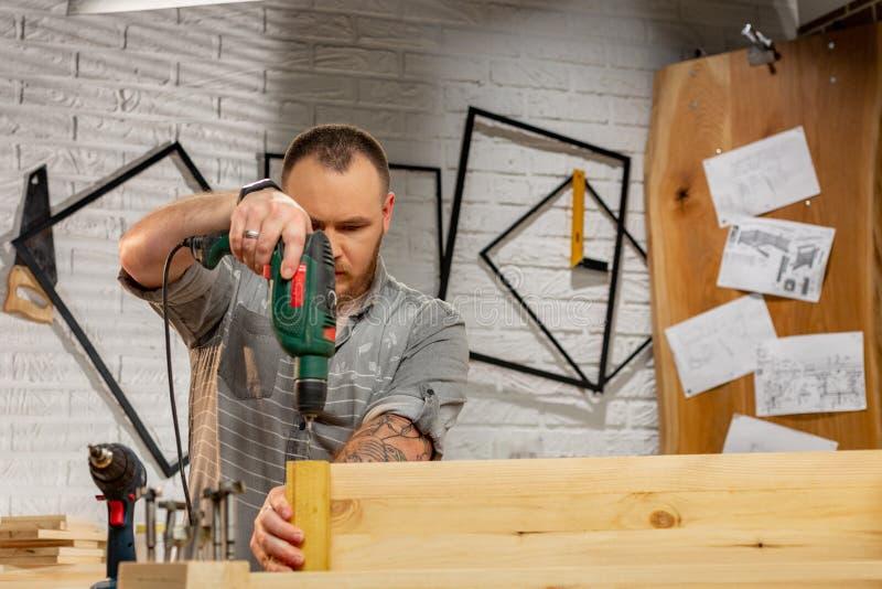 Conceito da profissão, da carpintaria, da carpintaria e dos povos - carpinteiro com a prancha de madeira da perfuração da broca e foto de stock royalty free
