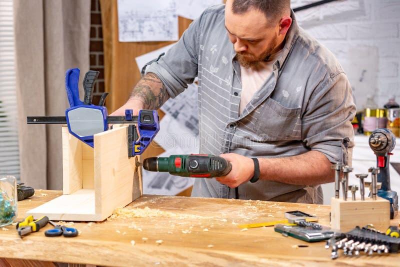 Conceito da profissão, da carpintaria, da carpintaria e dos povos - carpinteiro com a prancha de madeira da perfuração da broca e imagem de stock