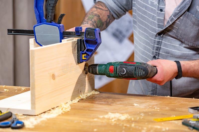 Conceito da profissão, da carpintaria, da carpintaria e dos povos - carpinteiro com a prancha de madeira da perfuração da broca e fotos de stock