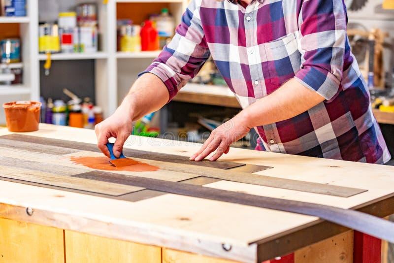 Conceito da profissão, da carpintaria, da carpintaria e dos povos - carpinteiro que trabalha com prancha de madeira imagens de stock royalty free
