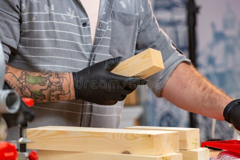 Conceito da profissão, da carpintaria, da carpintaria e dos povos - carpinteiro que trabalha com a prancha de madeira na oficina fotografia de stock royalty free