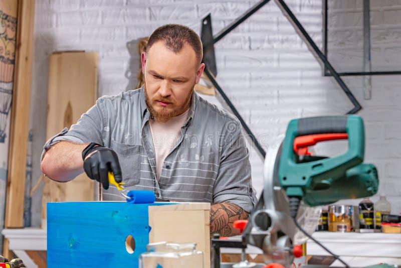 Conceito da profissão, da carpintaria, da carpintaria e dos povos - carpinteiro que trabalha com prancha e tampas de madeira ele  foto de stock