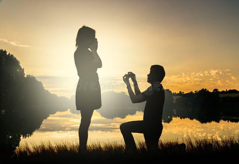 Conceito da proposta do casamento Os pares novos têm datar no sol ajustado fotografia de stock