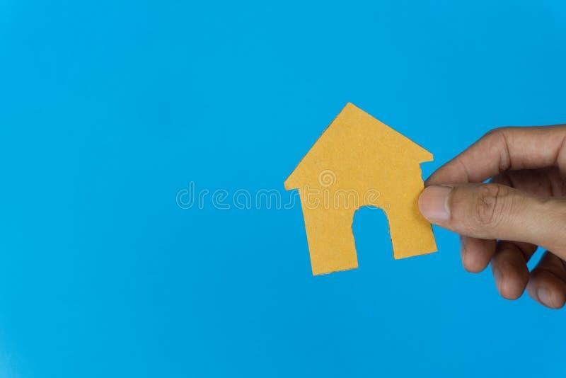 Conceito da propriedade Empréstimo hipotecário, hipoteca reversa, alojamento, negócio e finança Uma mão do homem que guarda a cas fotografia de stock royalty free