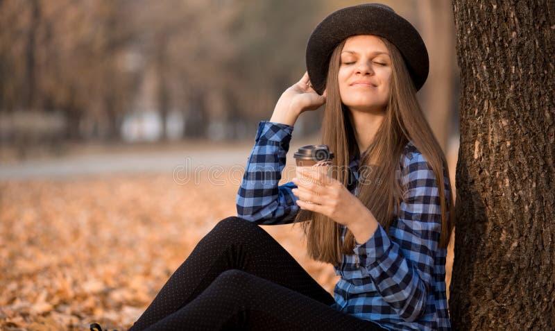 Conceito da queda Mulher feliz e alegre no chapéu, café bebendo ao sentar-se nas folhas do parque fotografia de stock