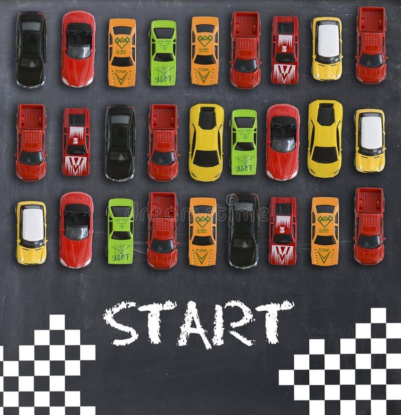 Conceito da raça ou da competição com os carros do brinquedo no quadro-negro imagem de stock royalty free