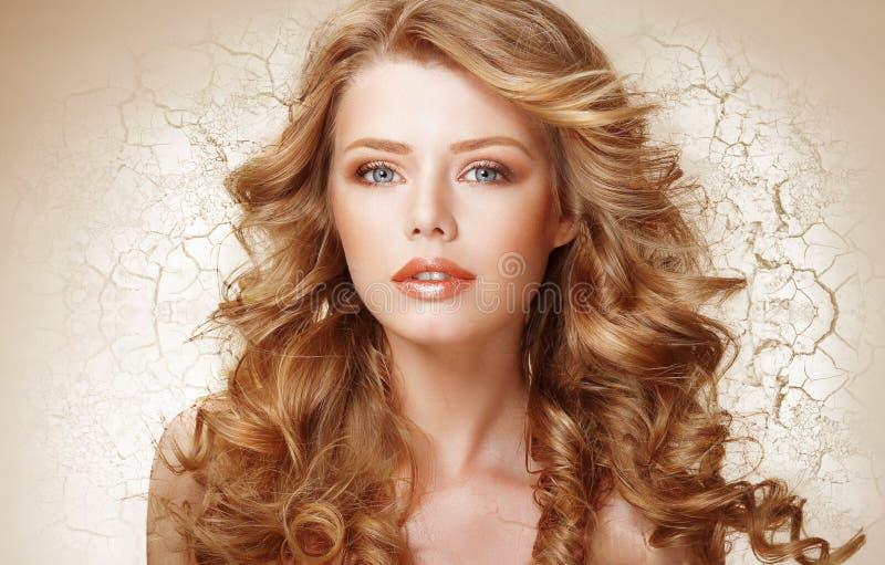 Conceito da recuperação Mulher com cabelo encaracolado sobre parede secada rachada (terra) foto de stock