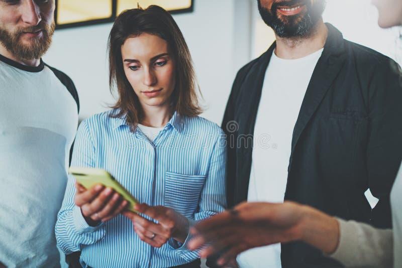 Conceito da reunião de negócios dos colegas de trabalho Jovens mulheres que guardam a mão do smartphone e notícias móveis da disc fotos de stock royalty free