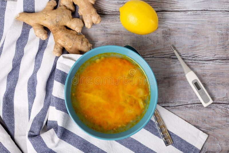 Conceito da saúde Bacia de caldo caseiro fresco da sopa para curar a gripe, doença, doente Limão, termômetro e gengibre no branco imagens de stock