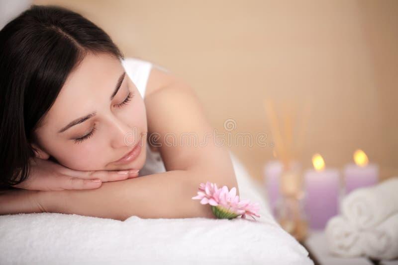 Conceito da saúde, da beleza, do recurso e do abrandamento - mulher bonita com os olhos fechados no salão de beleza dos termas qu foto de stock