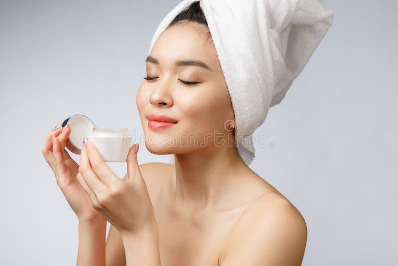 Conceito da saúde e da beleza - mulher asiática atrativa que aplica o creme em sua pele, isolada no branco imagens de stock