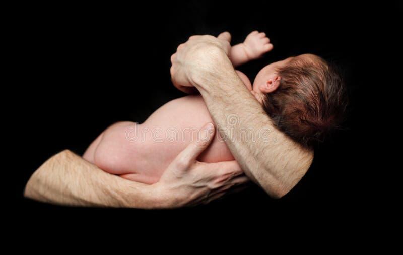 Conceito da segurança - bebê nas mãos do pai do conforto imagens de stock royalty free