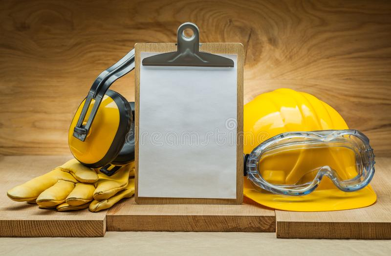 Conceito da seguran?a folha de papel vazia para o copyspace na prancheta capacete da construção e fones de ouvido amarelos das lu foto de stock