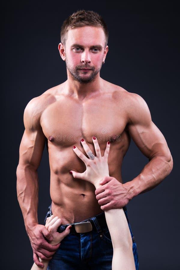 Conceito da sexualidade - homem muscular tocante das mãos fêmeas sobre o cinza imagem de stock royalty free