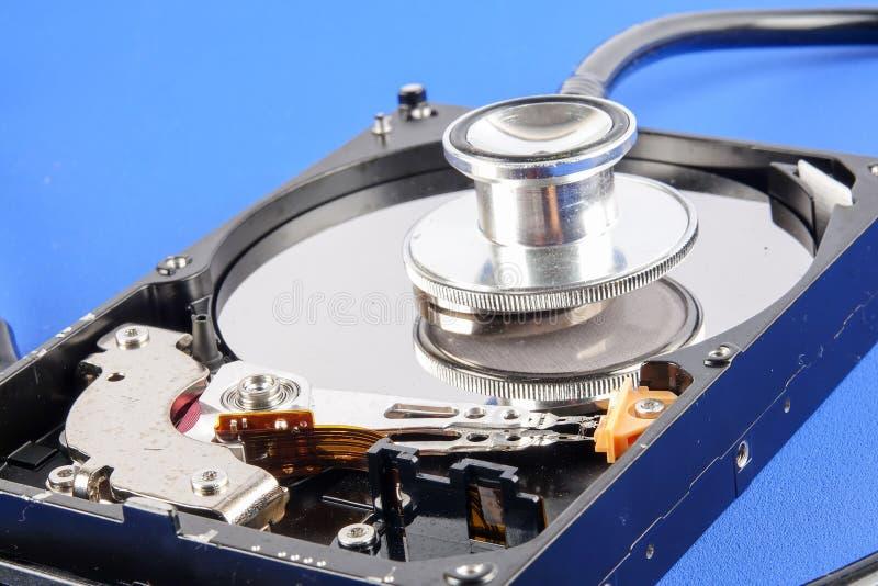 CONCEITO DA TECNOLOGIA DA RECUPERAÇÃO E DO REPARO: Movimentação de disco rígido HDD com o estetoscópio isolado em um fundo azul fotografia de stock