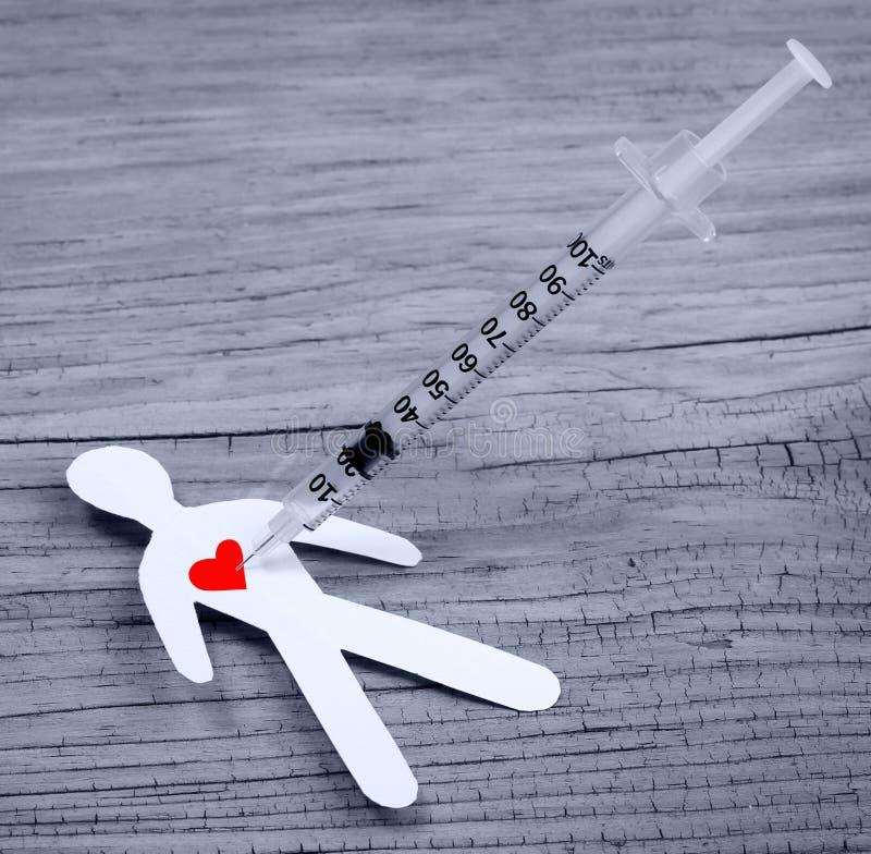 Conceito da toxicodependência. Homem de papel com coração e seringa fotografia de stock royalty free