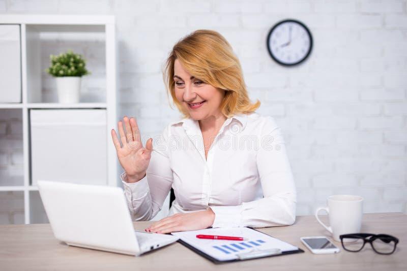 Conceito da videoconferência - retrato da mulher de negócio maduro que fala com sócios em linha fotografia de stock royalty free