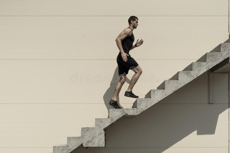 Conceito das ambições com as escadas de escalada do desportista foto de stock royalty free
