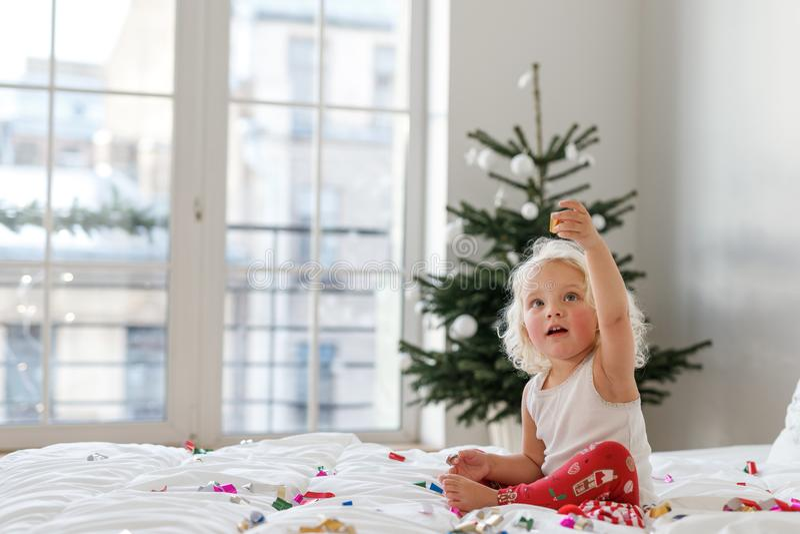 Conceito das crianças, do Natal e do ano novo A criança fêmea loura adorável veste os pyjamas, jogos com confetes coloridos sobre foto de stock royalty free