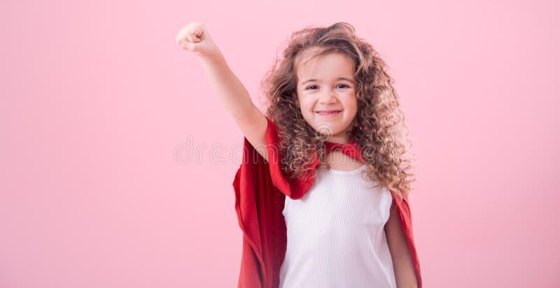 Conceito das crianças, menina de sorriso que joga o super-herói imagens de stock