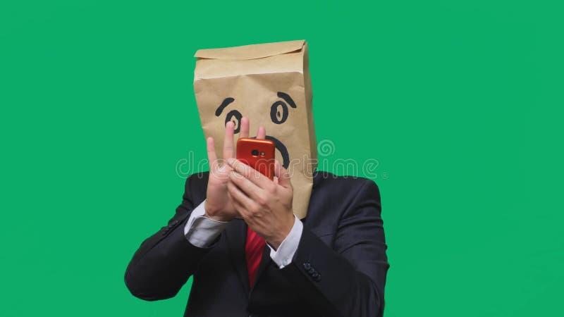 Conceito das emoções, gestos um homem com os sacos de papel em sua cabeça, com um emoticon pintado, medo Fala em um telefone celu imagens de stock royalty free