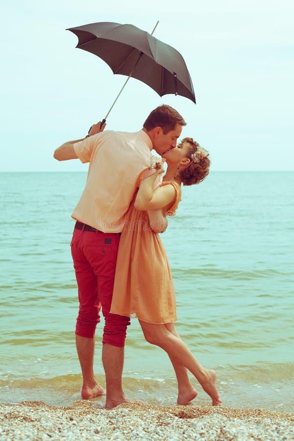 Conceito das férias de verão Acople a posição na praia perto da água, ho imagens de stock royalty free