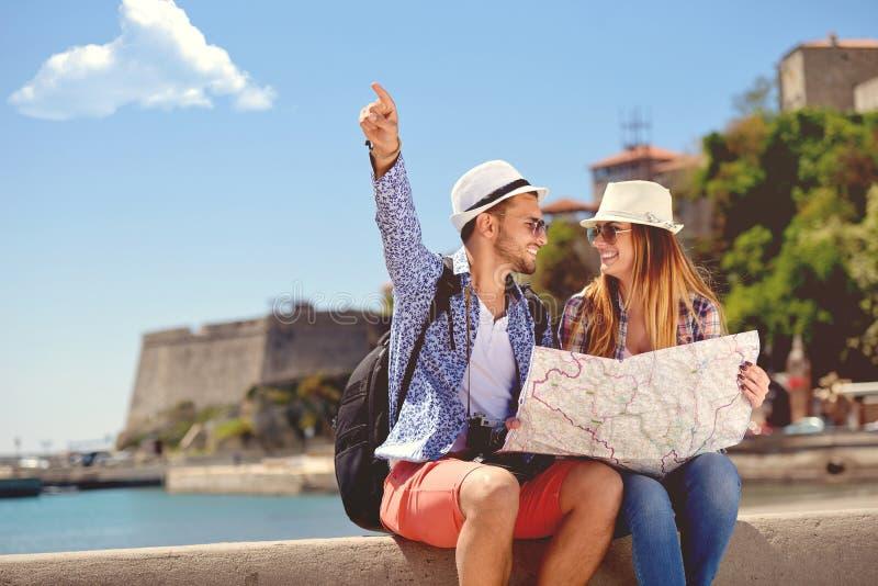 Conceito das férias de verão, datar e do turismo - par de sorriso nos óculos de sol com o mapa na cidade imagem de stock