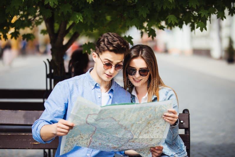 Conceito das férias de verão, datar e do turismo - turistas de sorriso dos pares nos óculos de sol com o mapa na cidade nova imagens de stock royalty free