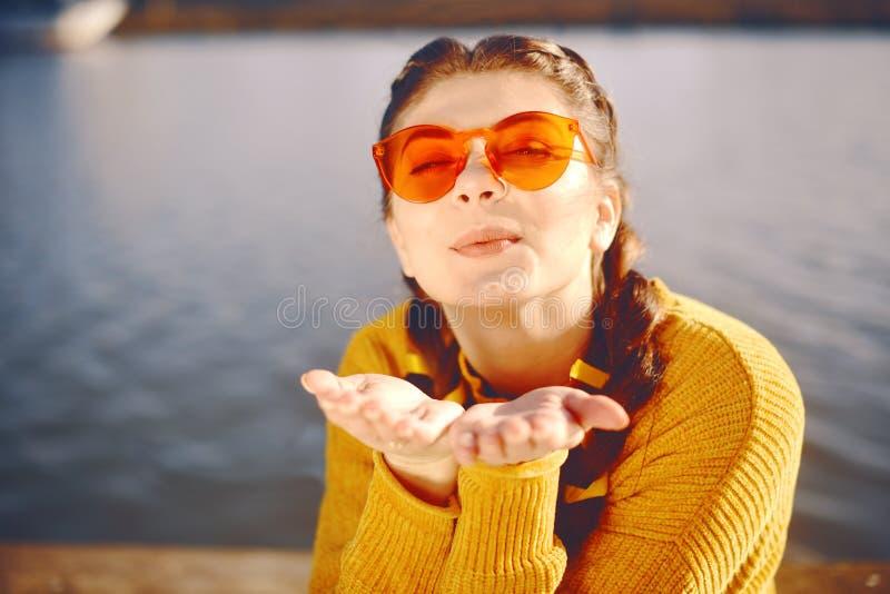 Conceito das férias de verão - a mulher feliz envia o beijo doce do ar Retrato positivo da sprint da jovem mulher alegre feliz Ve imagem de stock royalty free