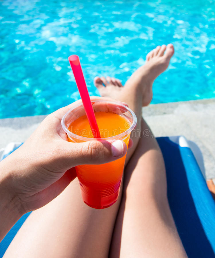 Conceito das férias de verão - pés e cocktail sobre a piscina b foto de stock royalty free