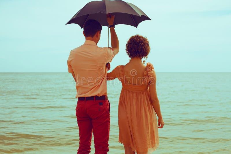 Conceito das férias de verão Pares que estão na praia perto da água e imagens de stock