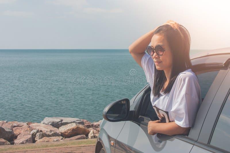 Conceito das férias e do feriado: Viagem feliz do carro de família nos óculos de sol vestindo do mar, da mulher do retrato e na f fotografia de stock