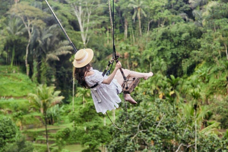 Conceito das férias Jovem mulher feliz no vestido branco e no chapéu que balançam no bosque da palma fotos de stock royalty free
