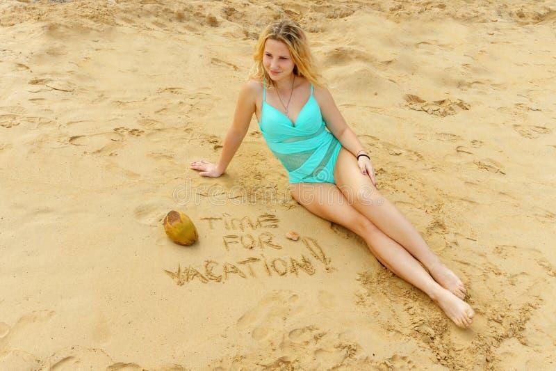 Conceito das férias menina bonita em um roupa de banho de turquesa na praia com cocos fotografia de stock