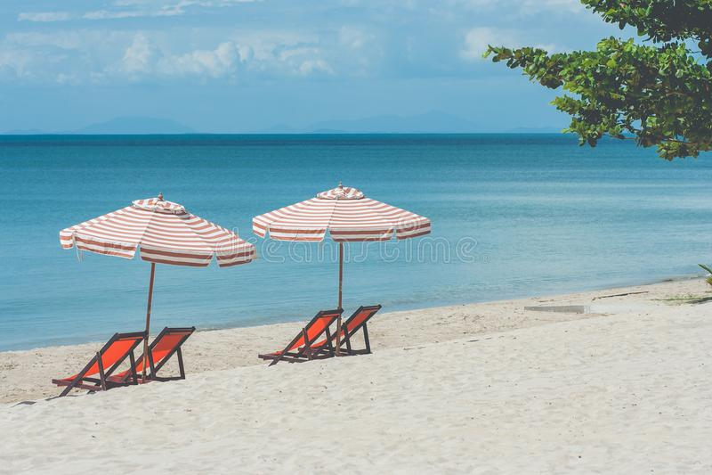 Conceito das férias: Quatro cadeiras e ajustes de madeira vermelhos do guarda-chuva de praia dois na areia branca com seascape no imagem de stock