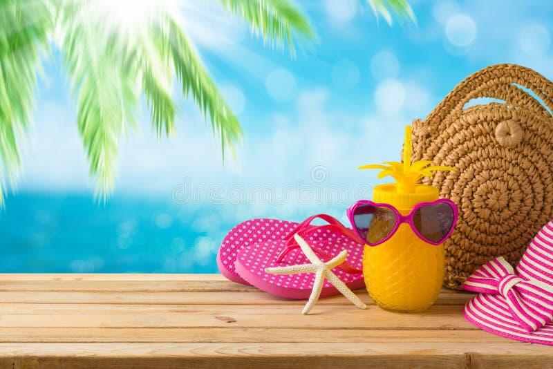Conceito das f?rias das f?rias de ver?o com suco de abacaxi, saco da forma da praia e falhan?os de aleta na tabela de madeira sob foto de stock